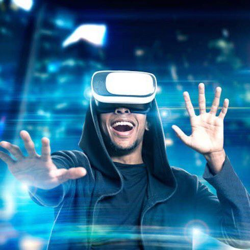 man with virtual reality glasses on smiling with hand out in front